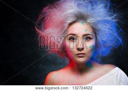 Portrait of the girl painter with color paint on face and disheveled colored hairs.