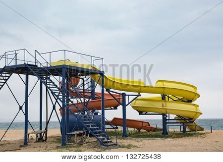 A water slide on an empty beach. The two tubes on the background of the sea