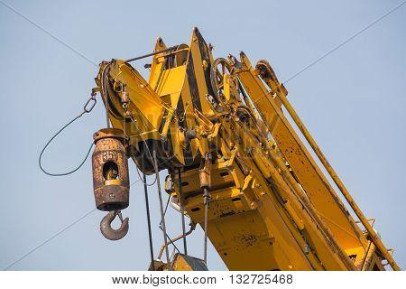 Big yellow crane arm with hook close-up