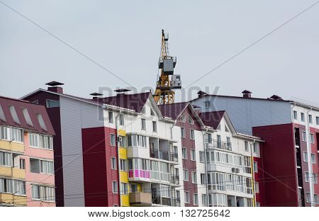 Colored residential home. Tower hoisting cranes over building
