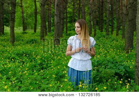 Portrait of beautiful girl in pine forest among flowers