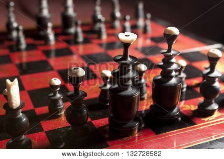 Carved wooden chess pieces with bone tips on a black and red board