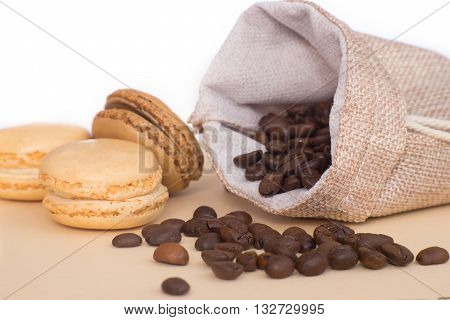 Coffee pouch with coffee grains next to cookies macaroons on pastel color table isolated on white background