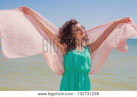 Young girl on the beach in summer in a beautiful dress with a flying scarf in hands