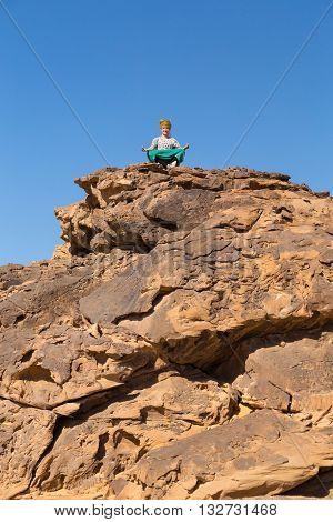 Tourist with turban meditating on big rock in dessert, Egypt.