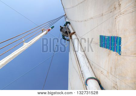 Man climbing mast on felucca, traditional wooden sailboat on Nile, Egypt.