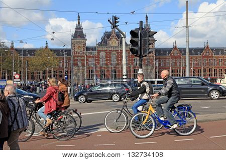 AMSTERDAM, NETHERLANDS - MAY 3, 2016: Local people on bicycles cross the road in front of Central Station in Amsterdam, the Netherlands. There are more bicycles then people in Amsterdam.