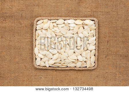 Frame made of rope with pearl pumpkin seed on sackcloth with place for your creativity