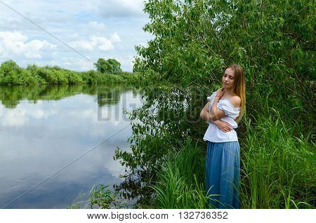 Portrait of a beautiful young woman on a river bank