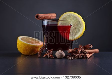 Mulled wine with spices on a black table