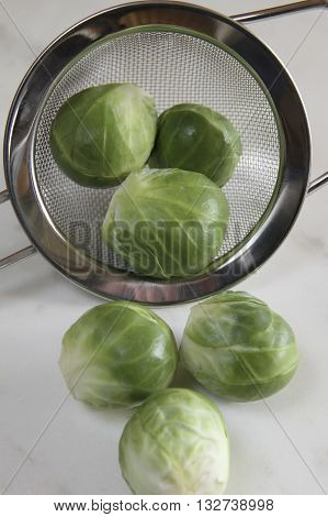 Some brussel sprouts in a sieve prepared for cooking.