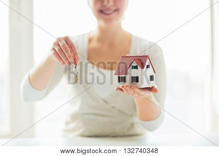 building, mortgage, real estate and property concept - close up of happy woman holding house model and home keys