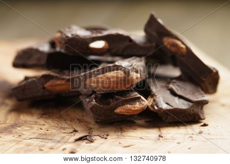 homemade dark chocolate with almond nuts on wooden board, shallow focus