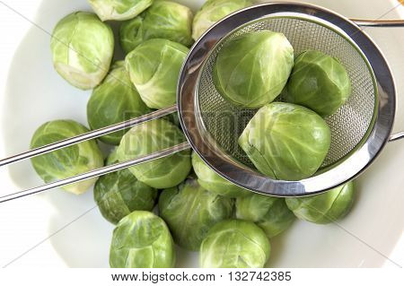 Some fresh brussel sprouts in a sieve.