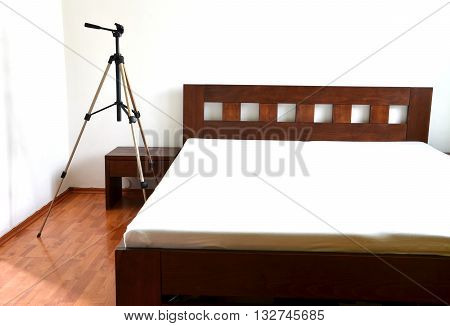 Tripod for camera next to the wooden bed in bedroom