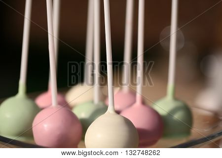 Sweet delicious colorful cake pops on sticks dessert for wedding party standing in rows on dark background