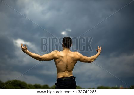 Young handsome man with muscular body and bare back posing outdoor on cloudy grey sky background with raised hands