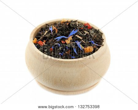 Black tea blend with dried fruits and cornflower in wooden bowl isolated on white background