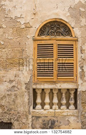 Facade of an old stone house. Window with an arch and yellow closed shutter. Decorative columns under the window. Senglea island Malta.