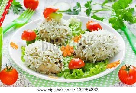 Baby healthy dinner: steamed hedgehogs meatballs with rice on vegetable garnish glade selective focus