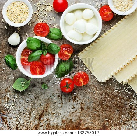 Ingredients for lasagna: fresh basil cherry tomatoes baby mozzarella cheese fresh pasta parmesan on old metal background blank space for text top view