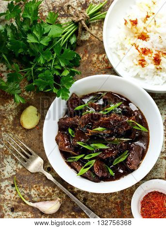 Homemade beef cooked in a traditional asian style on old metal background with ingredients top view