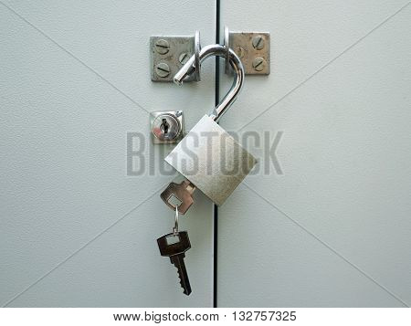 The metal lock with key on a door.