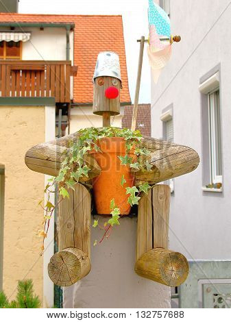 In the picture shows a hand-made wooden man in the form of attachment to vases of flowers.