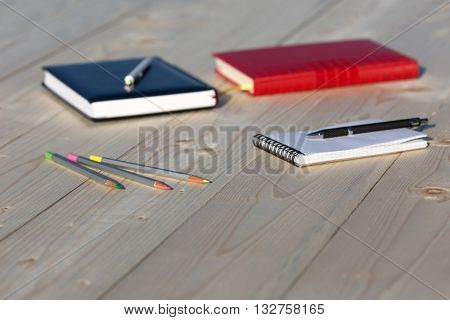 Several Business and Lifestyle Items on Fresh Raw Light Wood Desk Red and Blue Notepads Opened Sketchbook Color Pencils and Black Pen