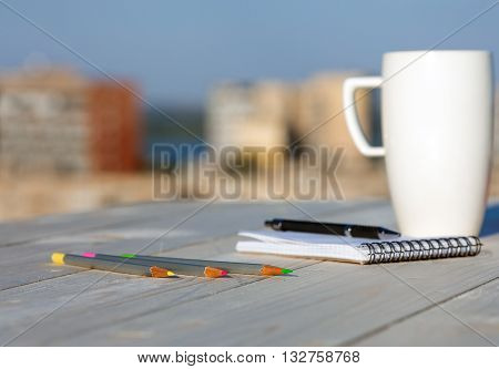 Business and Every Day Life Items on Wooden Desk Color Pencils Notepad Pen and White Coffee Mug