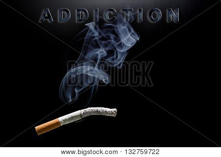 Burning cigarette smoke and text addiction on black background