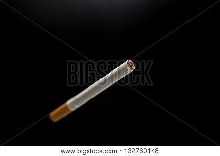 Only one blurred cigarette and black background
