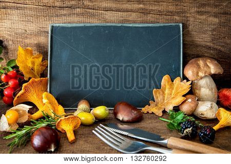 Thanksgiving still life with mushrooms, seasonal fruit and vegetables on wooden table with space for text.  Cooking concept