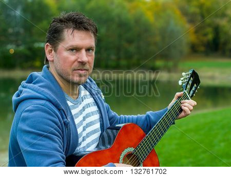 Mature bearded man playing red guitar in green park by the lake