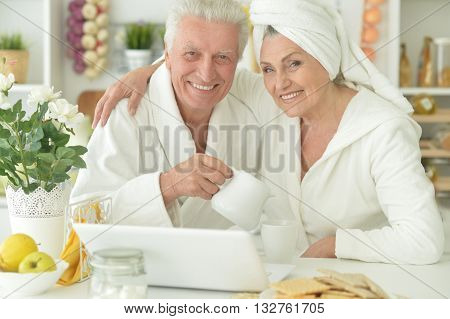 happy senior couple in a bathrobes with laptop  at home