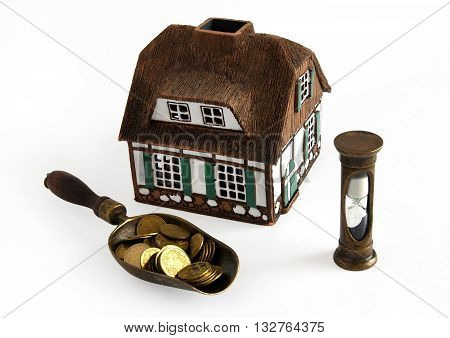 House model coins and hourglass symbolize the rapid favorable credit mortgages concept
