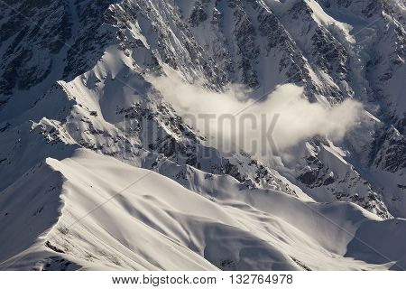 White cloud over snow mountain peaks on sunny weather