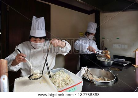 WUZHEN CHINA - MARCH 24: Unidentified Chinese people trade traditional food on March 24 2016 in Wuzhen China. Wuzhen is a historic scenic town located in northern Zhejiang Province China
