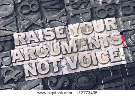 raise your arguments not voice exclamation made from metallic letterpress blocks with dark letters background