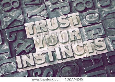 trust your instincts made from metallic letterpress blocks with dark letters background