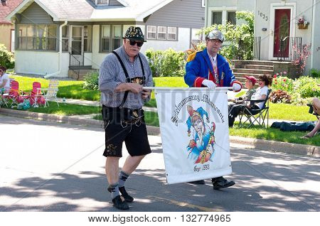 WEST ST. PAUL, MINNESOTA - MAY 21, 2016: Two members of German Karneval Club or Spielmannszug of Minnesota march with banner during annual West St. Paul Days Grande Parade on May 21, 2016.
