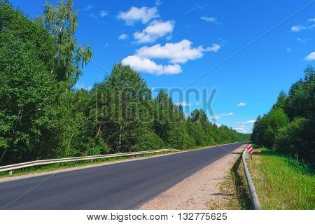 Empty highway with green forest on both sides