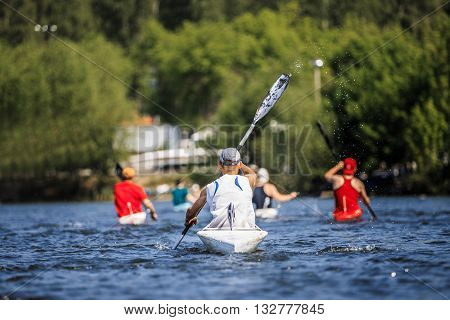 group of athletes canoeists boating on lake in a kayak. rear view