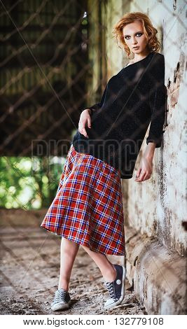 Grunge fashion: beautiful young girl in checkered skirt and blouse stands behind the lattice