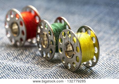 Rolls of sewing tread and blue jeans background with natural lighting.
