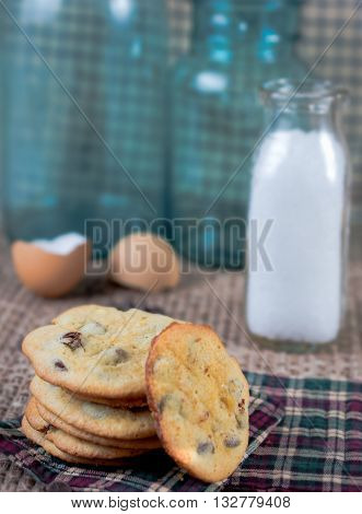 Chocolate chip cookies with milk.  Vintage blue jars in background