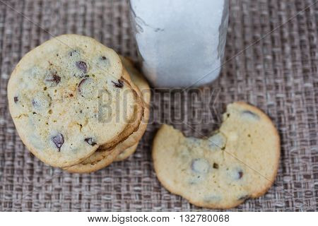 Chocolate chip cookies and milk.  One cookie has bite taken out of it.
