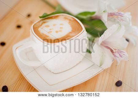 cup of coffee with milk and white flower