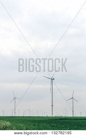 Wind turbines of windmills generating electricity for the city. Yard of windmill power generator under blue sky, shown as energy industry concept.