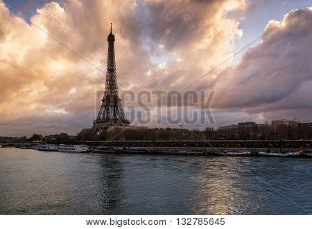 Luminous clouds, Eiffel Tower and the Seine River at sunrise. Port de Suffren, Paris, France